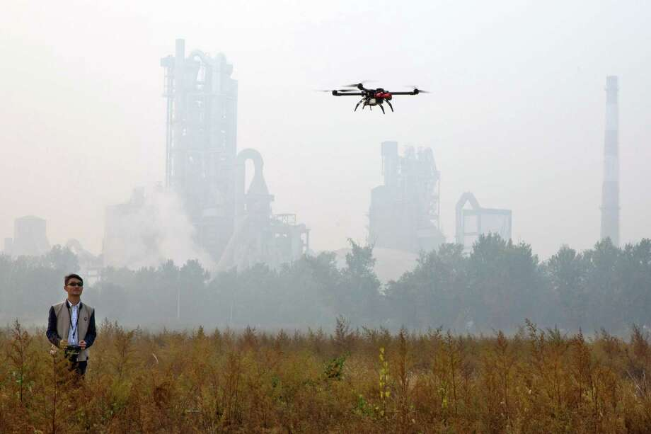 In this Oct. 17, 2015 photo, a Chinese man flies his drone near a cement factory during a polluted day in Beijing. TT Aviation Technology Co. - and their instructors - are part of a new cottage industry sprouting up in China, where drones are being deployed in rising numbers and touted as a game-changer in agriculture, logistics, film production and law enforcement. (AP Photo/Ng Han Guan) Photo: Ng Han Guan, STF / AP