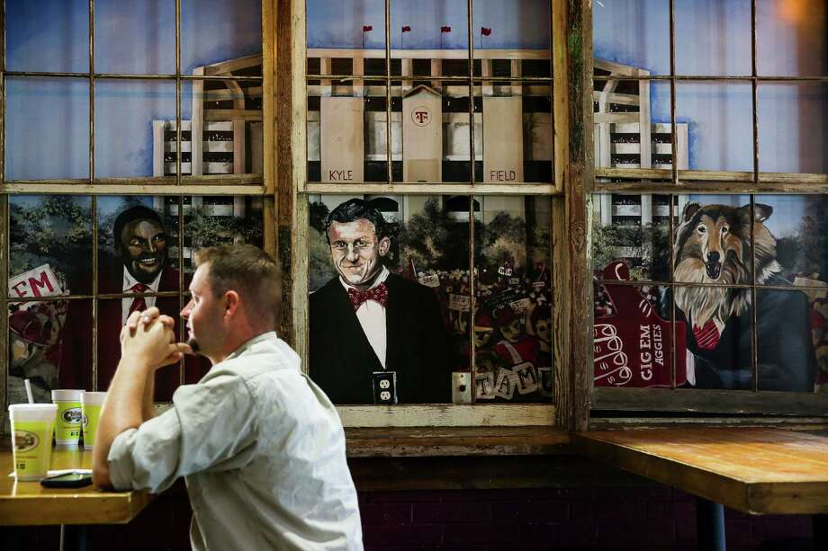 A patron sits in front of a Johnny Manziel mural at Chimy's Cerveceria, a College Station eatery where Manziel reportedly ordered a round of drinks on the house the night he was drafted. Photo: Photos By Michael Ciaglo / Houston Chronicle / © 2016  Houston Chronicle