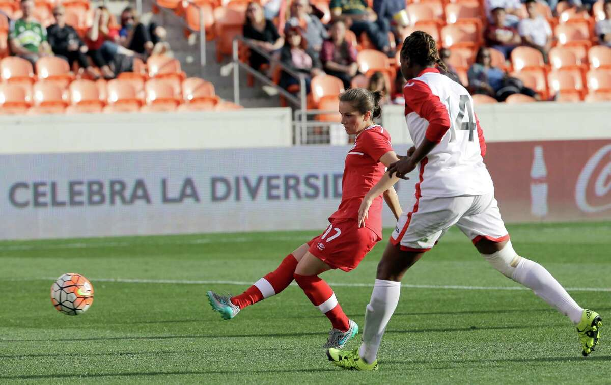 Canada's Jessie Fleming (17) shots to score a goal as Trinidad & Tobago's Karyn Forbes (14) defends during the second half of a CONCACAF Olympic qualifying tournament soccer match Sunday, Feb. 14, 2016, in Houston. Canada won 6-0. (AP Photo/David J. Phillip)
