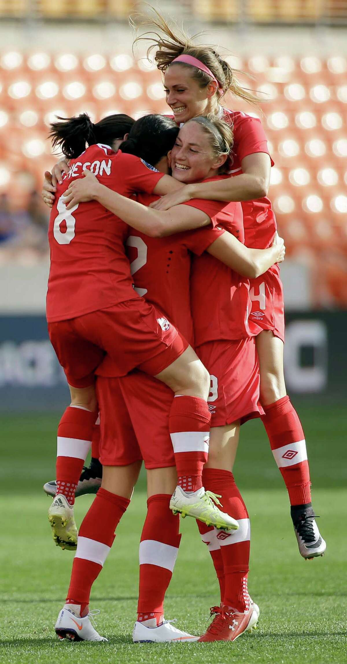 Canada's Christine Sinclair, second from left, is mobbed by teammates Diana Matheson (8), Janine Beckie, right, and Shelina Zadorsky (4) after scoring a goal against Trinidad & Tobago during the second half of a CONCACAF Olympic qualifying tournament soccer match Sunday, Feb. 14, 2016, in Houston. Canada won 6-0. (AP Photo/David J. Phillip)
