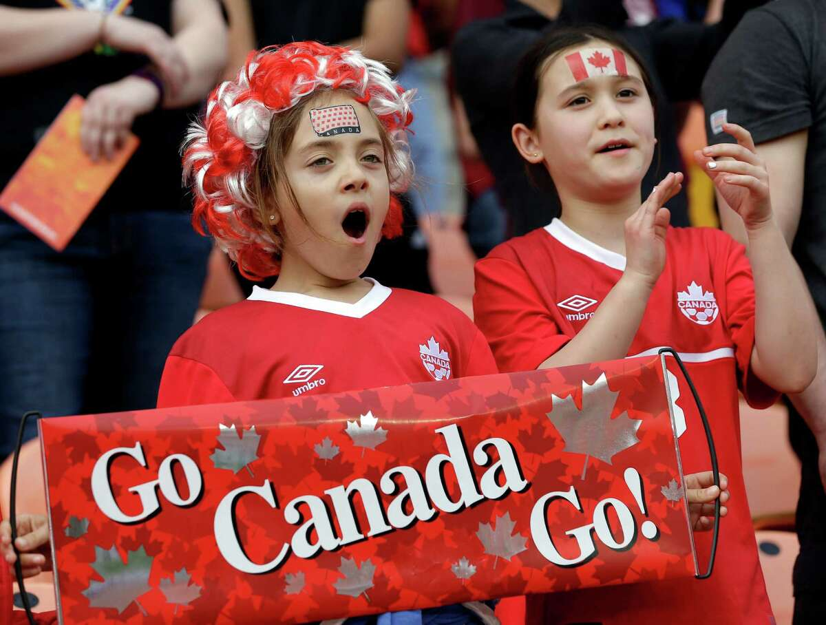 Alexa Calenti, left, and Chloe Hollott-Lo cheer for Canada's women's soccer team as they take the field for a CONCACAF Olympic qualifying tournament soccer match against Trinidad and Tobago Sunday, Feb. 14, 2016, in Houston. Canada won 6-0. (AP Photo/David J. Phillip)