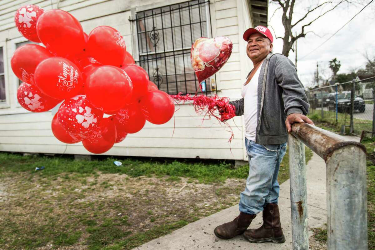 Alfredo Morales holds a bundle of red Valentine's balloons before as he waits to deliver them to family on Sunday, Feb. 14, 2016, in Houston.