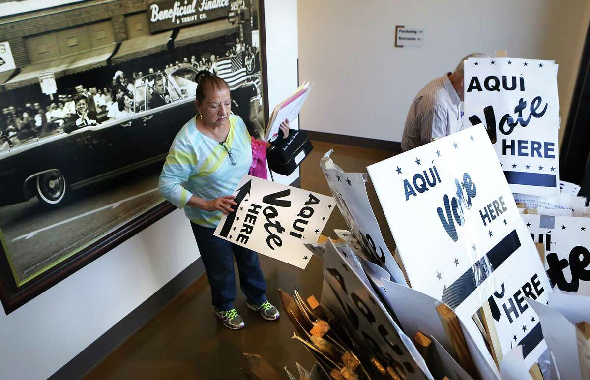 Esther Gill, a co-judge at a precinct in East Central, picks up extra signs following a training session for Bexar County election officials at Bexar County Election Department on Friday, Feb. 12, 2016. Behind Gill is a photo of John F. Kennedy's motorcade as it travels through downtown San Antonio the day before he was killed in Dallas.