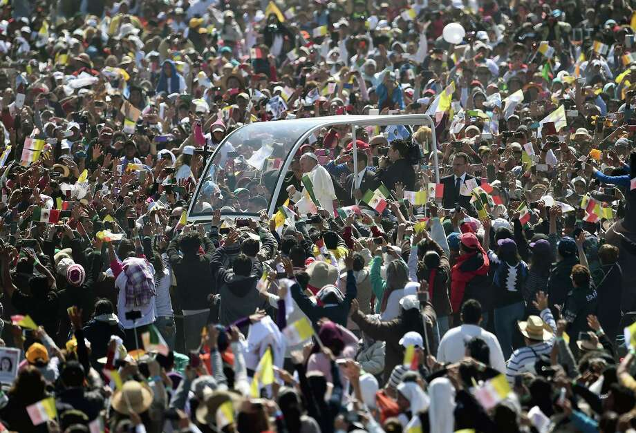 Pope Francis waves from the popemobile upon arrival to celebrate an open-air mass in Ecatepec, a rough, crime-plagued Mexico City suburb, during the second full day of his five-day trip to Mexico. Photo: Gabriel Bouys /Getty Images / AFP