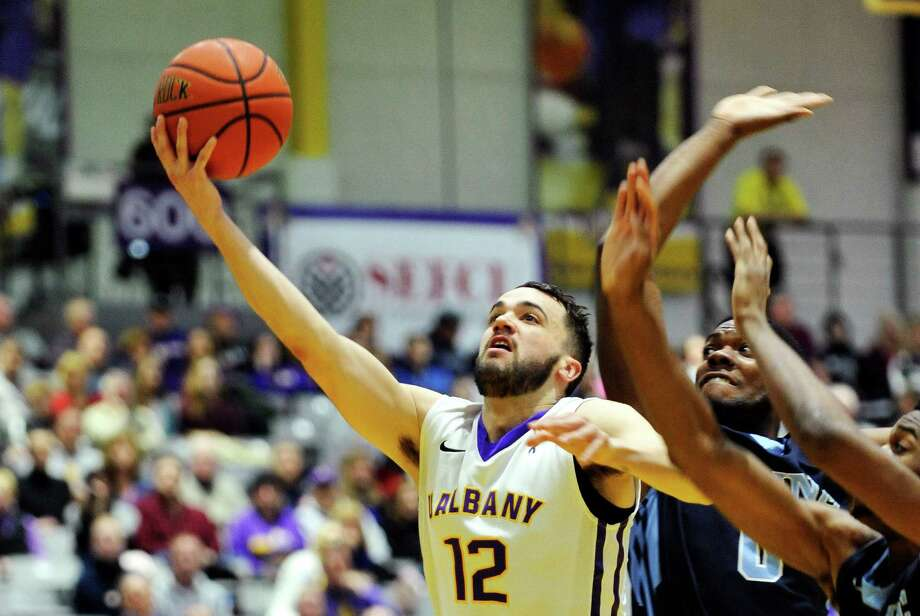 Peter Hooley of the UAlbany puts up a shot around two Maine players during their game on Sunday, Feb. 14, 2016, in Albany, N.Y.  (Paul Buckowski / Times Union) Photo: PAUL BUCKOWSKI / 10035422A