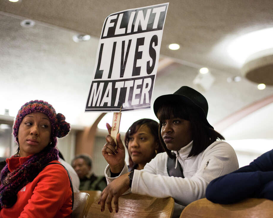 Dominique Strong, 30, Flint, Mich., holds up a sign during a city council meeting at Flint City Hall on Wednesday, February 3, 2016. Strong is from the North of Flint, one of the areas most effected by the city's ongoing water crisis due to economic mobility of the residents who live there. Photo: Brittany Greeson / For The Washington Post Via Getty Images / 2016 The Washington Post