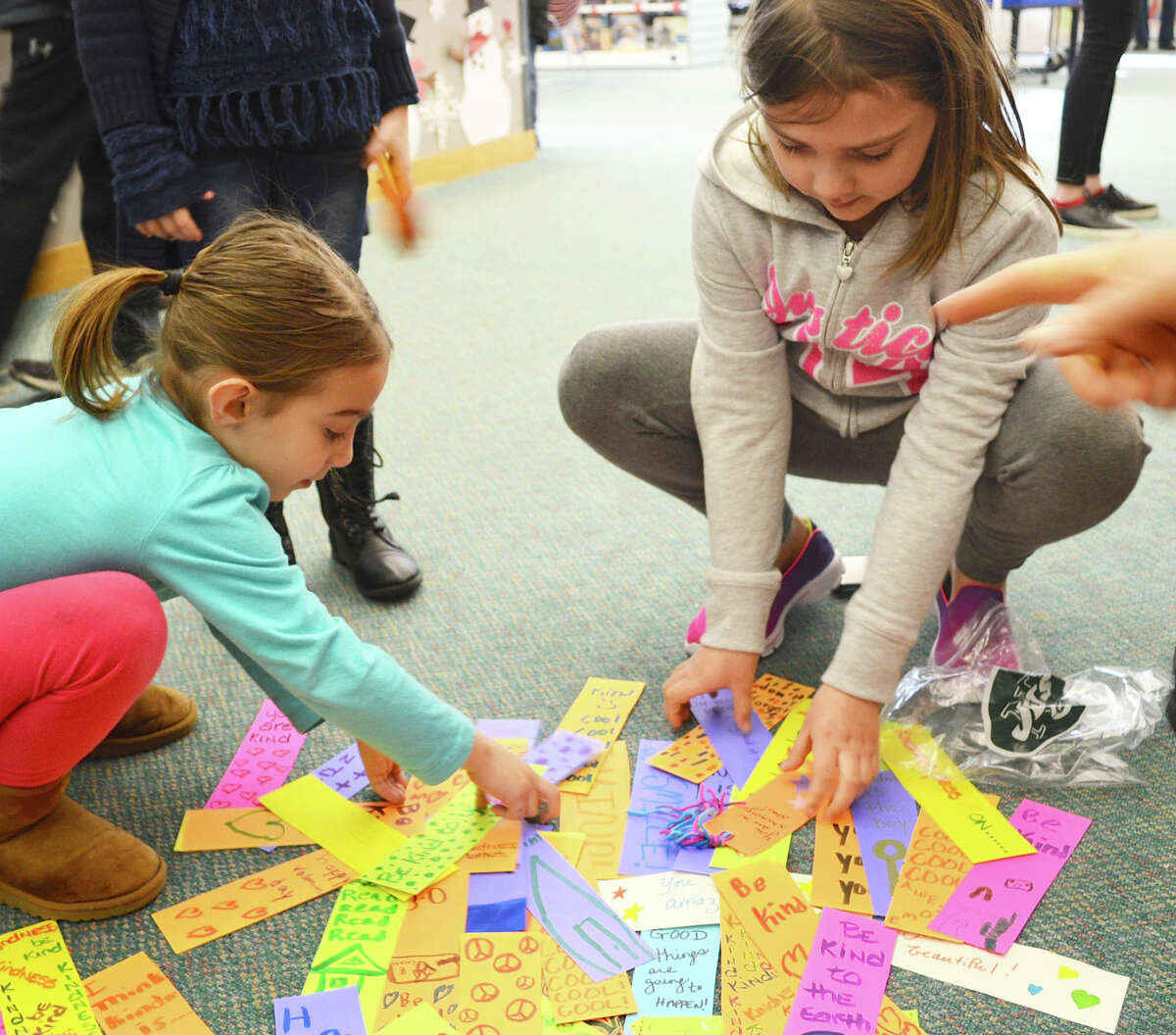 Grace Mollica, 7, left, and Lauren LaRose, 9, collect bookmarks at Fairfield Woods Branch Library to be placed in books to surprise readers with messages promoting acts of kindness.