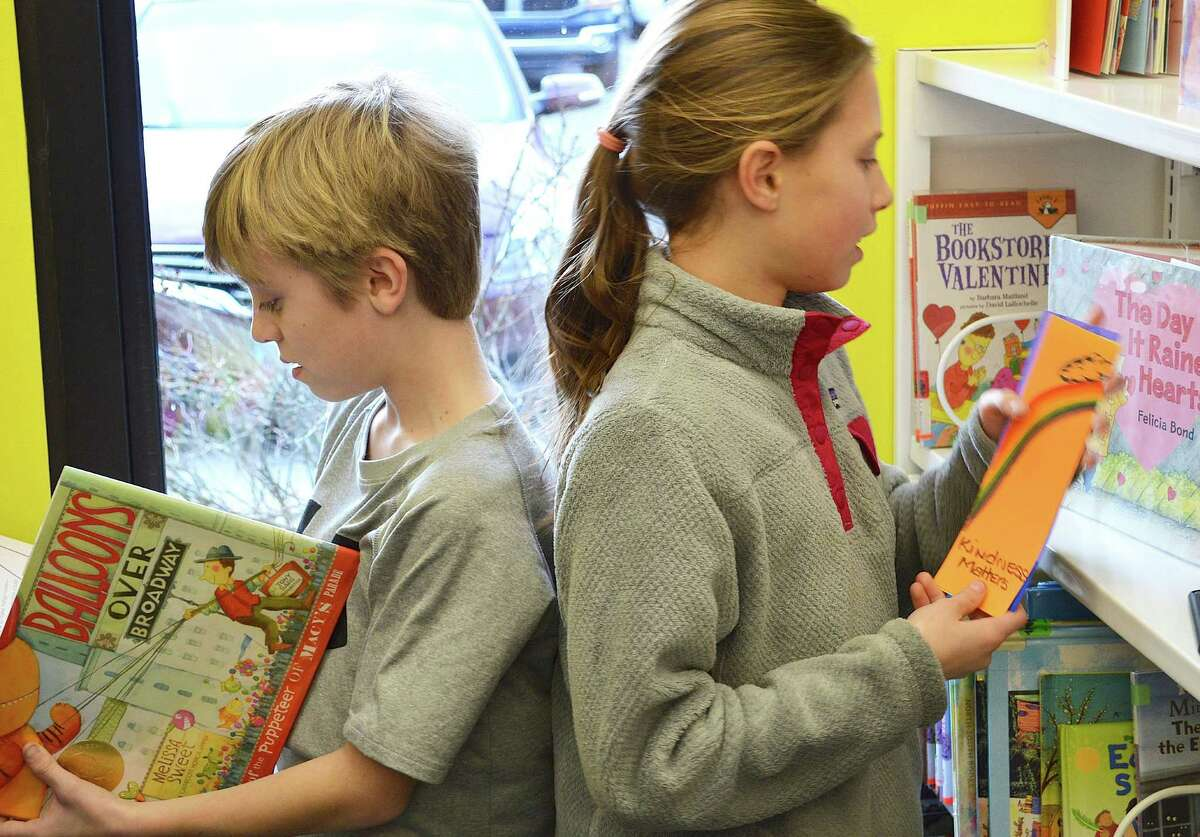 Meg Barnouw, 10, right, decides on a kindness bookmark for a particular volume at Fairfield Woods Branch Library, while Nicky Faustini, 11, takes a closer look at a selection.