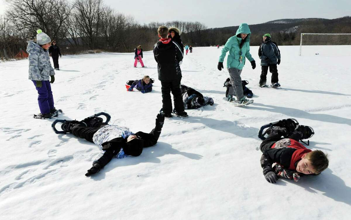 Walking in snowshoes can be exhausting as some fifth-graders found at Sarah Noble Intermediate School in New Milford Friday, Feb. 12, 2016. The Pratt Nature Center is holding Snowshoe Project 2016. This is the second year the center is holding the event and plans to take all New Milford third, fourth and fifth-grade students snowshoeing starting on Friday, Feb. 12, 2016, at Scotts Ridge Intermediate School. The event aims to promote living a healthy and active lifestyle.