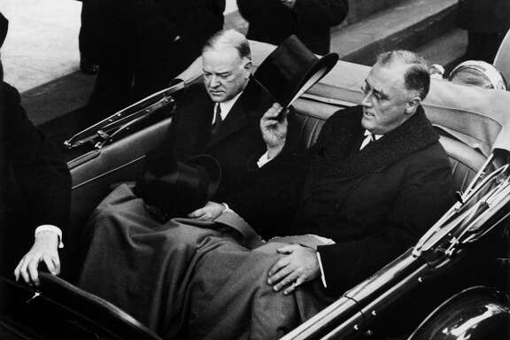 March 1933:  President Roosevelt (1882 - 1945) tips his top hat while sitting in the back of a car with former President Herbert Hoover (1874 - 1964) at the inauguration in Washington D.C.