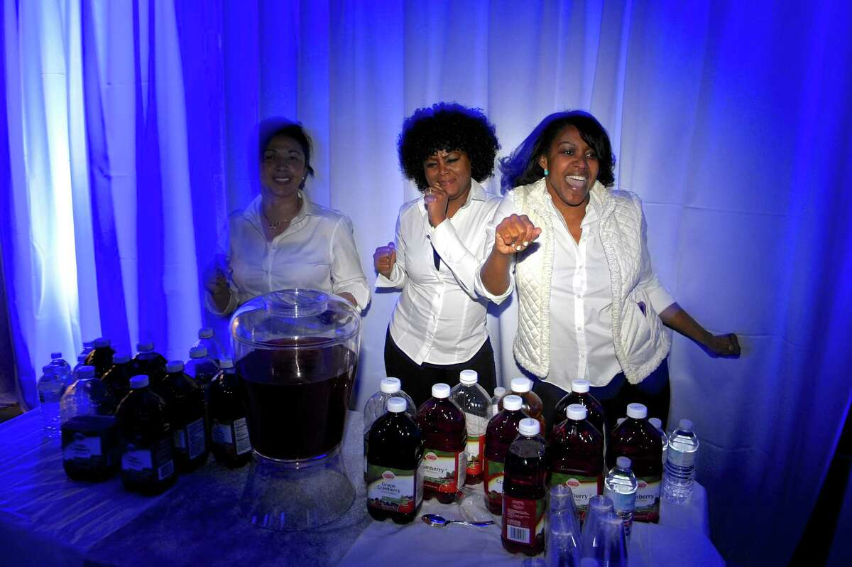 """From left, volunteers Jessie Ceci, of Brookfield; Janice Russell-Hines, of Danbury; and Arlene Campbell-Moore, of Bridgewater, dance to a song while manning a drink table during the """"Night to Shine Prom"""" on Friday."""
