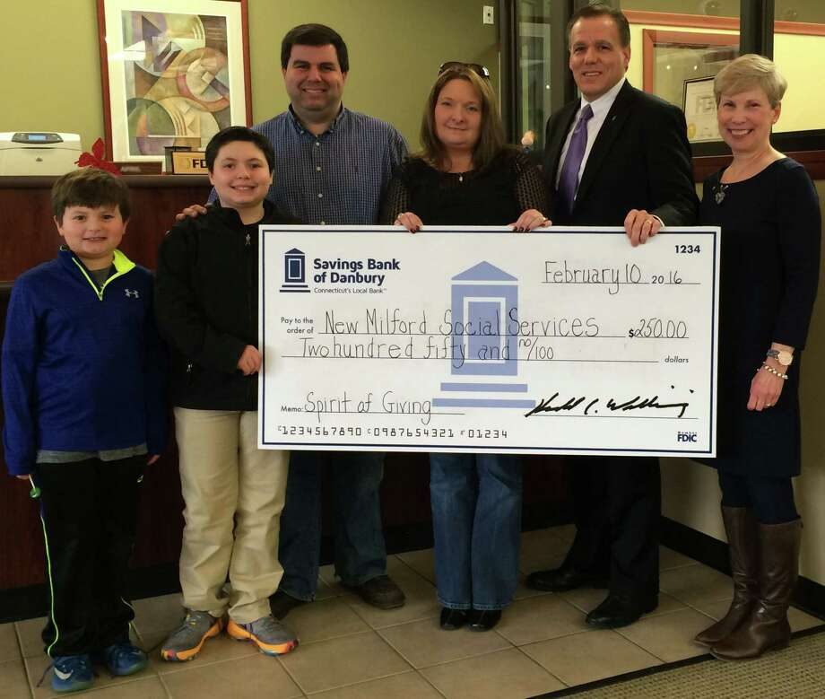The Vochis family, Alex, Nicholas, Stella and Michael, with Martin Morgado, COO Savings Bank of Danbury, and Beth Ann Fetzer, Community Development Officer Savings Bank of Danbury. The Vochis won the bank's Spirit of Giving holiday program. Photo: / Contibuted Photo