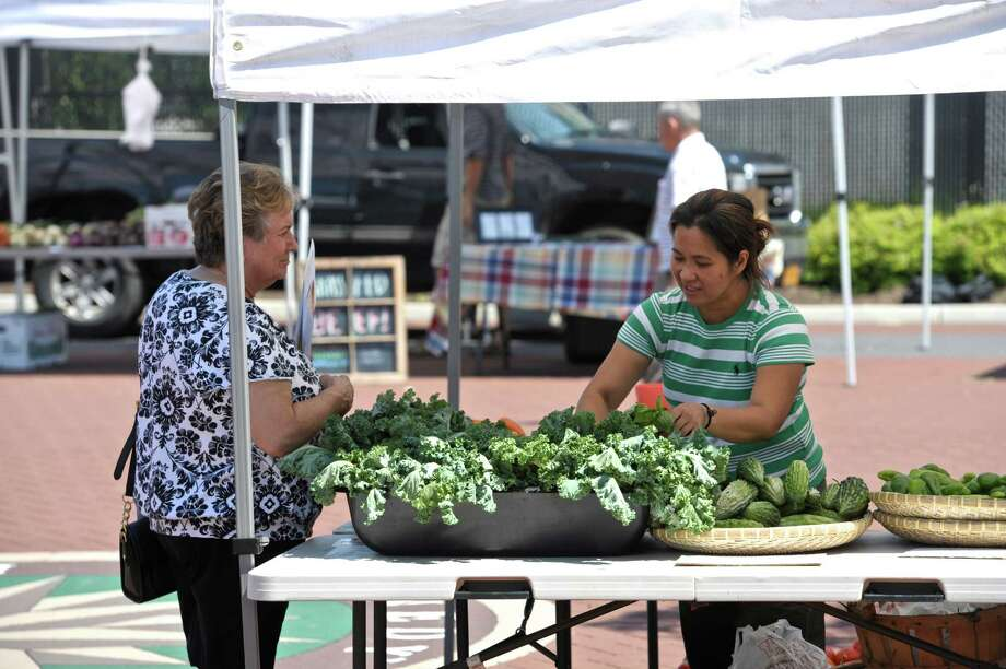 File photo of the Danburt Farmers' Market. Maria Lima, of Danbury, talks with Jannette Riego de Dios, at the Mother's & Son's booth at the CityCenter Danbury Farmers Market on Aug. 14, 2015, in Danbury, Conn. Photo: H John Voorhees III / Hearst Connecticut Media / The News-Times
