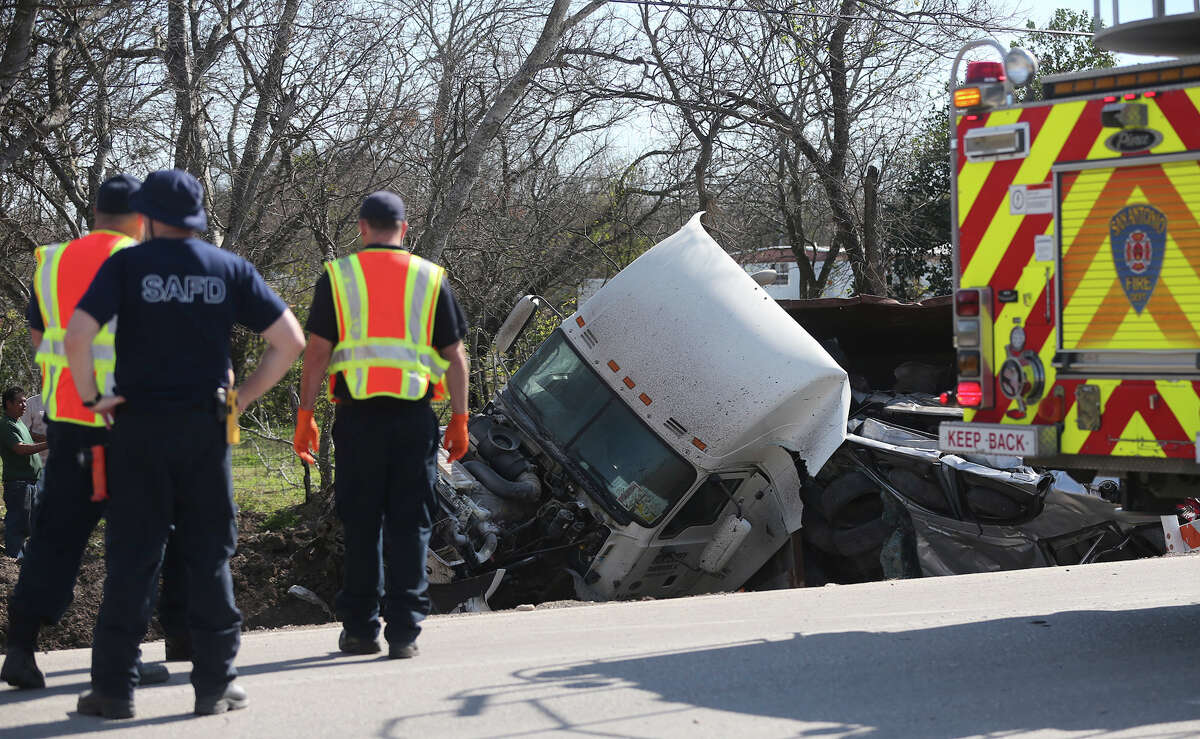Firefighters monitor the scene of an 18-wheeler crash Monday February 15, 2016 on the 8500 block of New Laredo Highway. A witness at the scene said a northbound SUV and an 18-wheeler carrying compacted cars collided about 2:00 p.m.. The driver of the 18-wheeler was not injured and the driver of the SUV was transported to an area hospital.