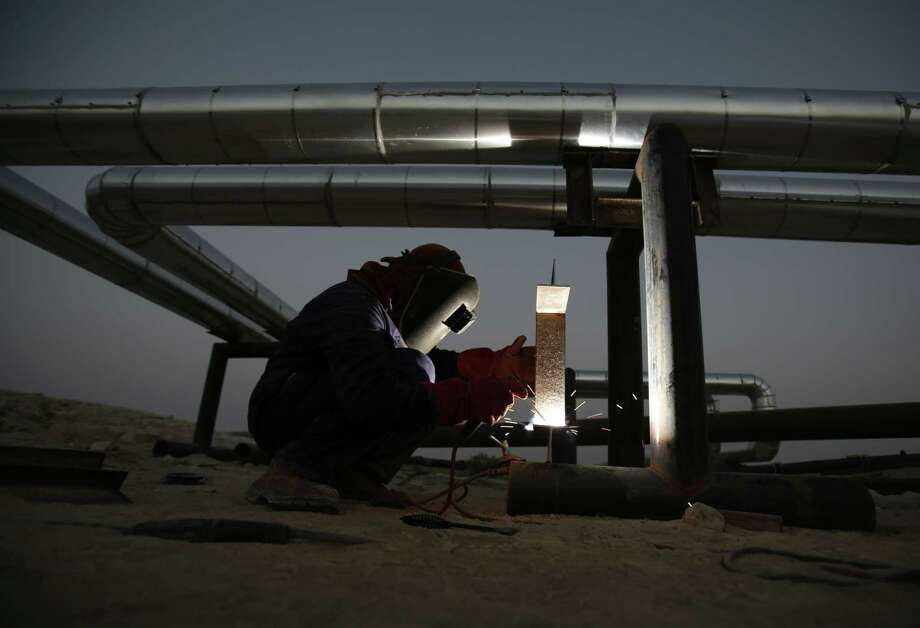 An oil field employee welds a pipeline in the desert oil fields of Sakhir, Bahrain.All is not well within OPEC as the oil cartel focuses on how much crude to pump for the rest of the year. Photo: Hasan Jamali /Associated Press / AP