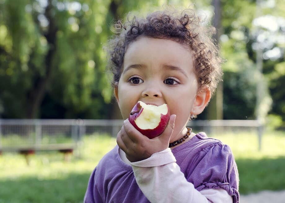 Child child eating an apple in a park in nature. Child child eating an apple in a park in nature. Photo: Pavla Zakova - Fotolia / Pavla Zakova - Fotolia