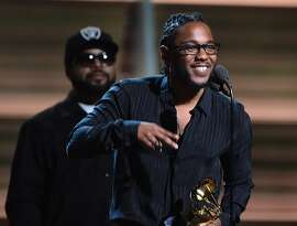 Recording artist  Kendrick Lamar (R) recieves the award for the Best Rap Album, To Pimp A Butterfly as Ice Cube looks on onstage during the 58th Annual Grammy music Awards in Los Angeles February 15, 2016.