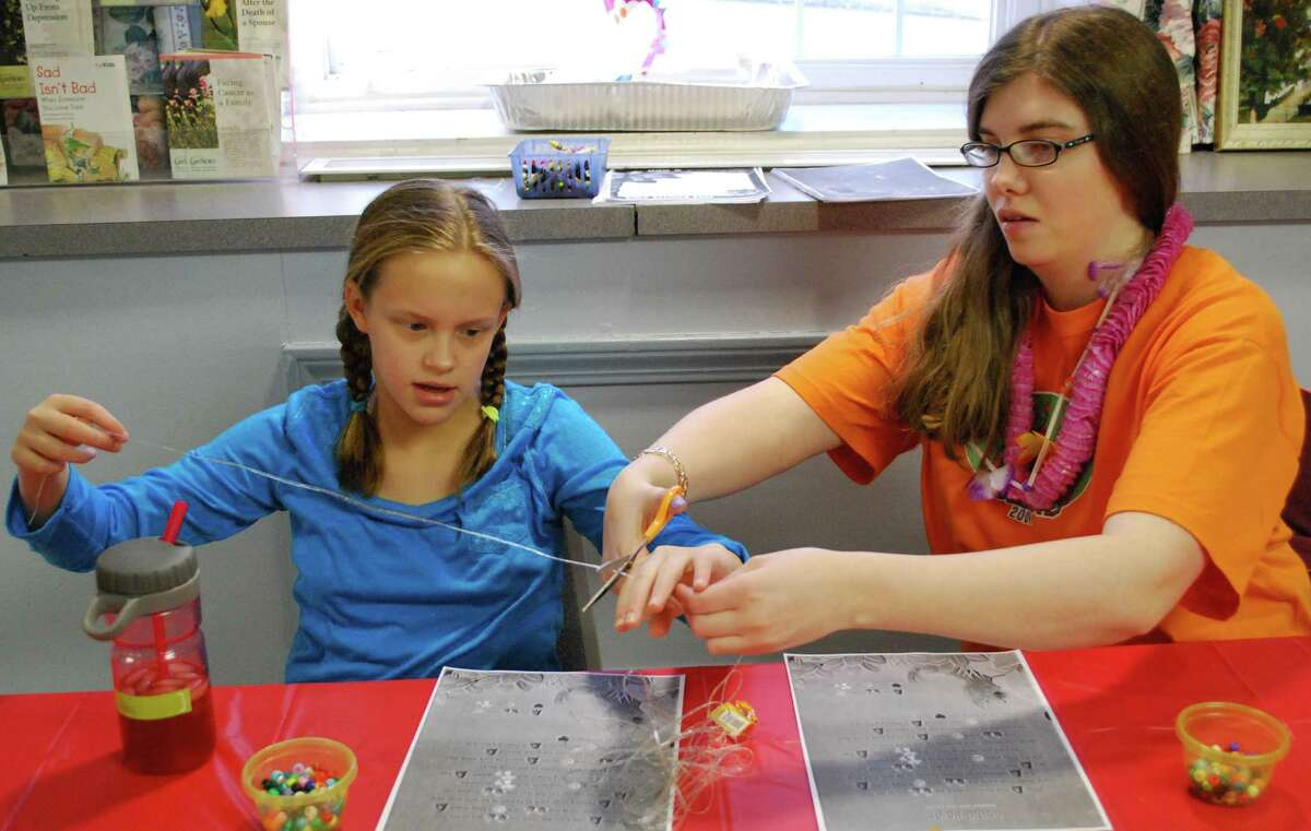 Spectrum/Abby Davis, 11, and Katie McKay, head up the craft table as they prepare necklace strings for Vacation Bible School participants at the First Congregational Church in New Milford's recently one-night VBS event to kick off the its year-long celebration of the church's 300th anniversary. Jan. 30, 2016