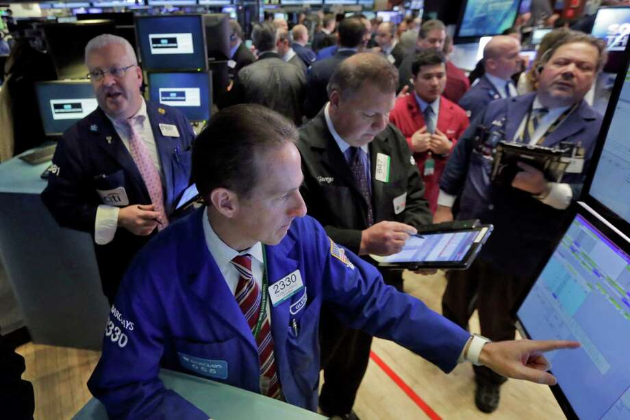 Specialist Glenn Carell, foreground, works with traders at his post on the floor of the New York Stock Exchange. Photo: Richard Drew /Associated Press / AP