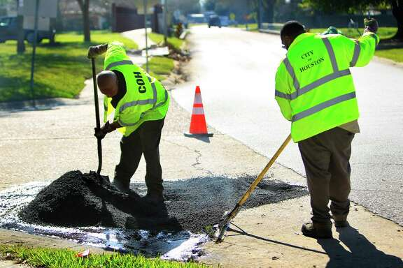 City workers repair a pothole last month. In January, crews filled 1,705 citizen-identified potholes.