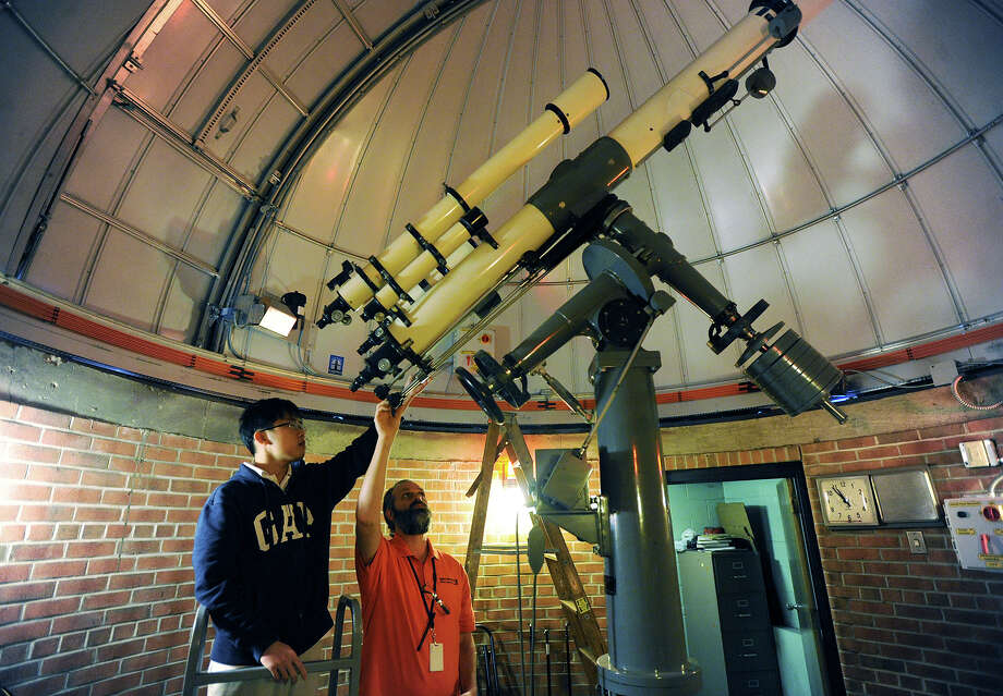 Bassick High School astronomy teacher Brian O'Shea demonstrates the operation of the school's telescope to senior Minh Deng, 17, in the school's observatory in Bridgeport. A new Ash 5 meter dome was recently installed atop the observatory. Photo: Brian A. Pounds / Hearst Connecticut Media / Connecticut Post