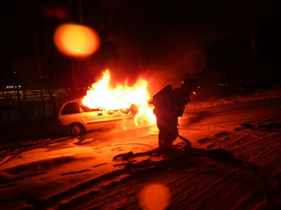 Fire crews battle a fully involved car fire on Padanaram Avenue Monday night. Photo: Contributed / Bernie Meehan