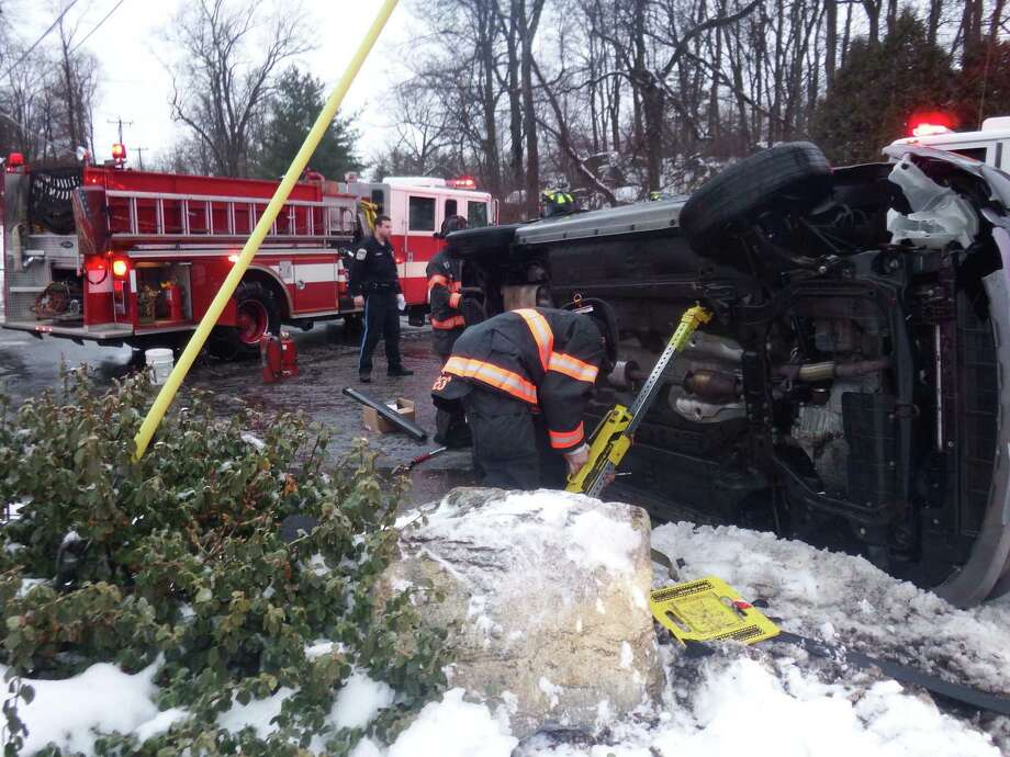 Fire crews work to stabilize a minivan that overturned on Barnum Road Tuesday morning. Photo: Contributed / Bernie Meehan