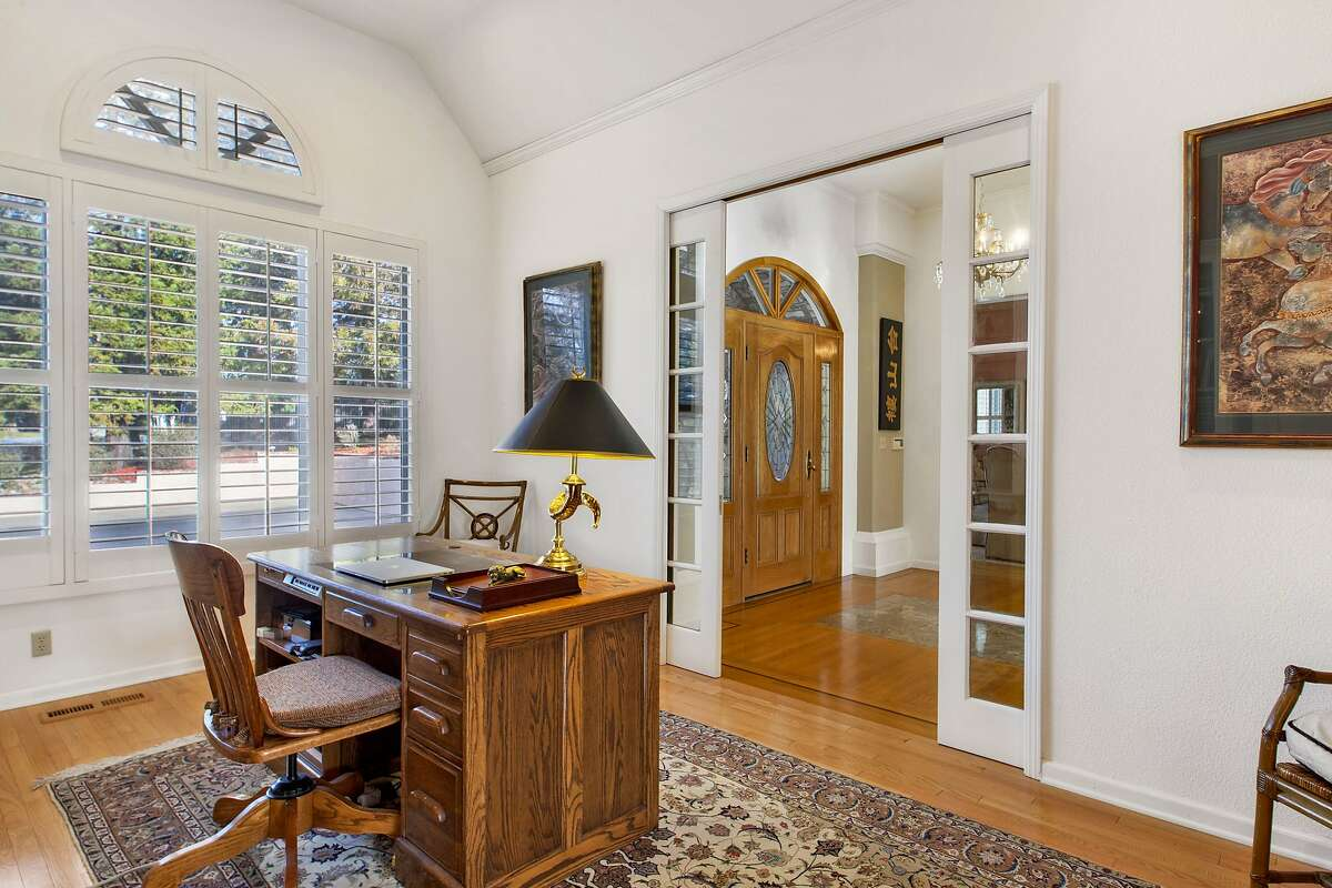 Pocket doors off the foyer sequester an office with a half-moon clerestory window.