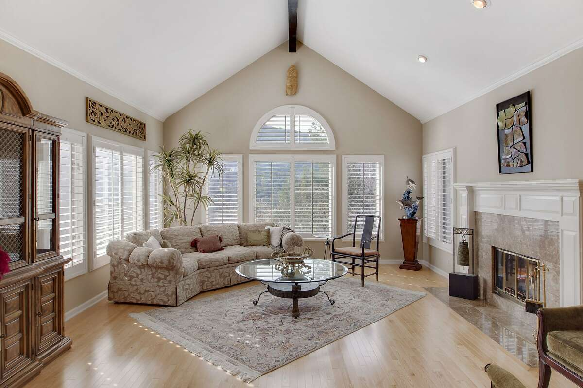 A formal living room enjoys windows on three sides, a stone surround for the fireplace and a vaulted, beamed ceiling.