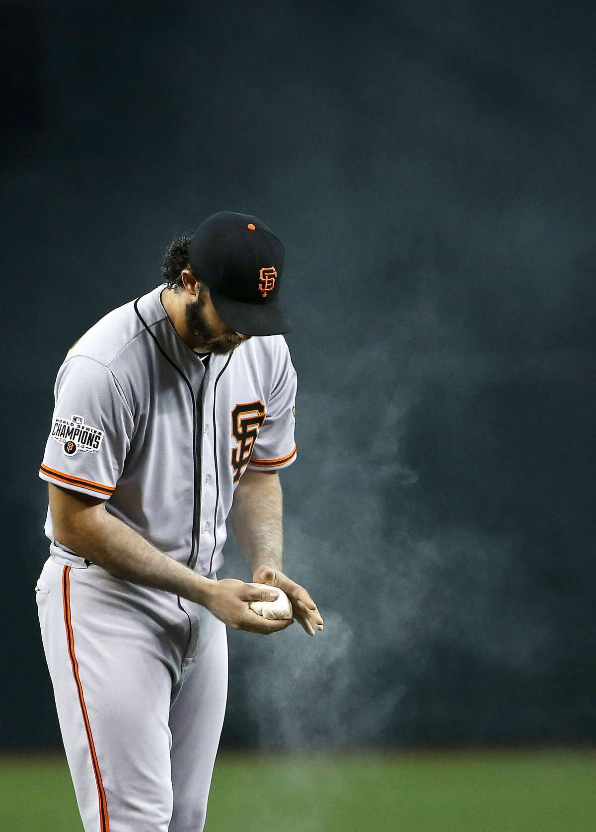 Madison Bumgarner applies rosin to his hand and arm during a game against the Arizona Diamondbacks in July 2015.