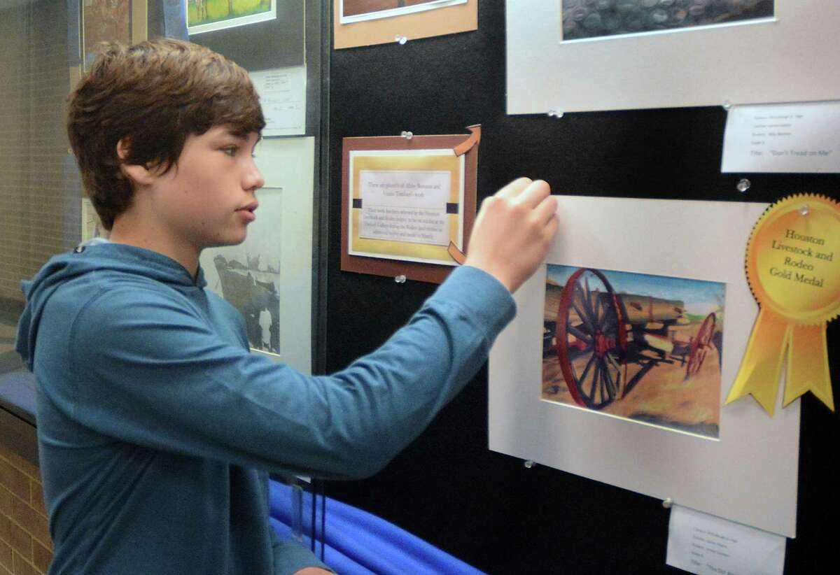 McCullough Junior High student Vinnie Tombari hangs a copy of his winning drawing in the school's art display case. Tombari won a Gold Medal for his drawing of a wagon at the Conroe ISD Art Show and will have his artwork on display at the Houston Livestock Show and Rodeo. Photograph by David Hopper