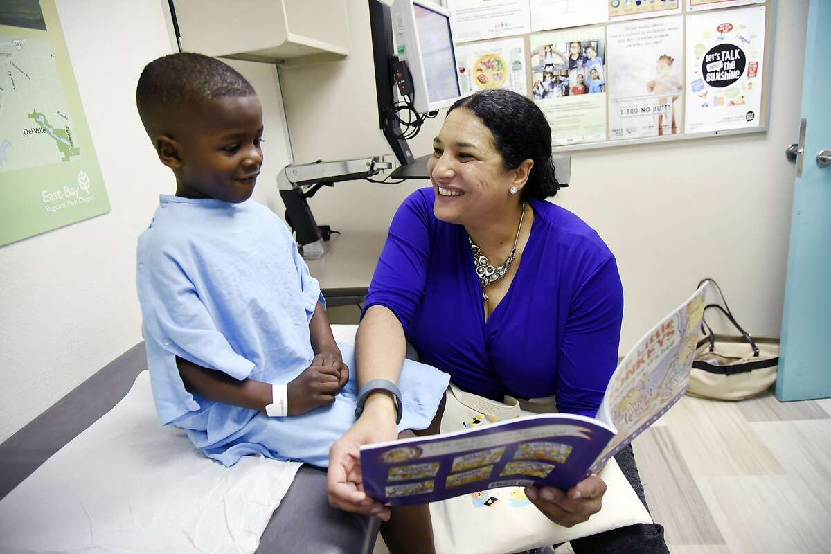 """Dr. Dayna Long shows a book from the Opportunity Institute's """"Talk, Read, Sing"""" program to patient Jason Walker, 5, during his checkup visit to UCSF Benioff Children's Hospital Oakland Primary Care Clinic in Oakland, CA Tuesday, February 16, 2016."""