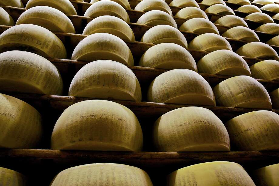 Parmigiano Reggiano cheeses sit on storage racks during the aging process at Il Trionfo cheese makers in San Secondo Parmense, Italy. In the United States, some grated Parmesan suppliers have been mislabeling products by filling them with too much cellulose, a common anti-clumping agent made from wood pulp, or using cheaper cheddar. Photo: Gianluca Colla /Bloomberg News / Copyright 2013 Bloomberg Finance LP