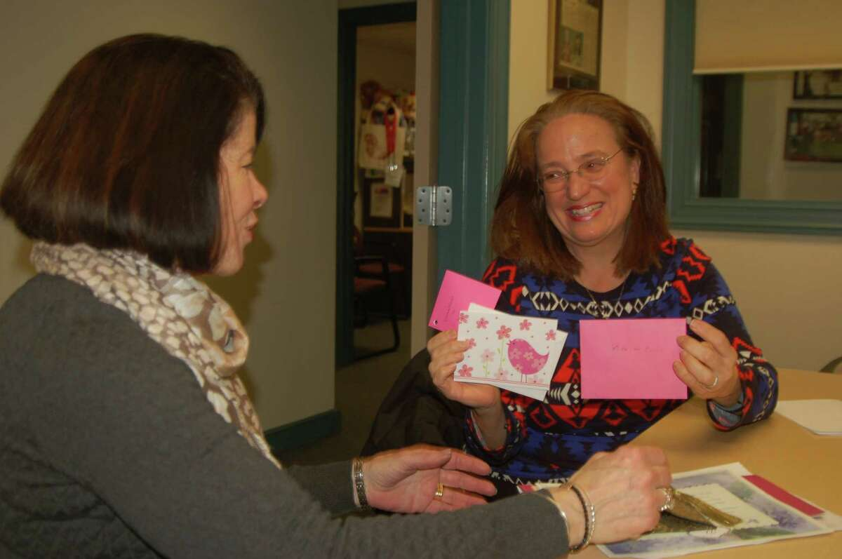 Joan Stewart Pratt, at right, presents a valentine signed by Kids in Crisis supporters to the organization's Executive Director Shari Shapiro.