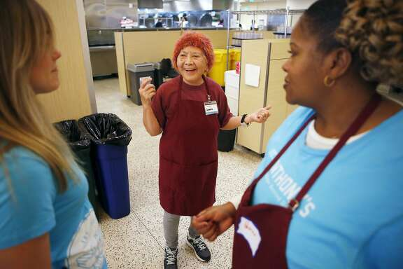 Carmelita Lozano chats with Katherine Rutledge, left, and Patricia Davis, right, about dancing to the music while volunteering in the dining room at St. Anthony's in San Francisco Tuesday February 16, 2016. Carmelita is 91-years-old and volunteers once a week at St. Anthony's.