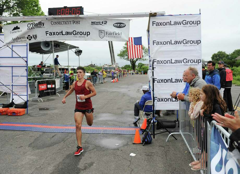 New Fairfield's John Raneri, the first Connecticut finisher, crosses the finish line in the Faxon Law Group Fairfield Half Marathon at Jennings Beach in Fairfield, Conn. Sunday, June 28, 2015.  Gosa Girma Tefera, of Ethiopia, was the first place overall finisher with a time of 1:04:05 and Etaferahu Temesgen, of Ethiopia, was the first female finisher with a time of 1:14:09. Photo: Tyler Sizemore / Hearst Connecticut Media / Greenwich Time