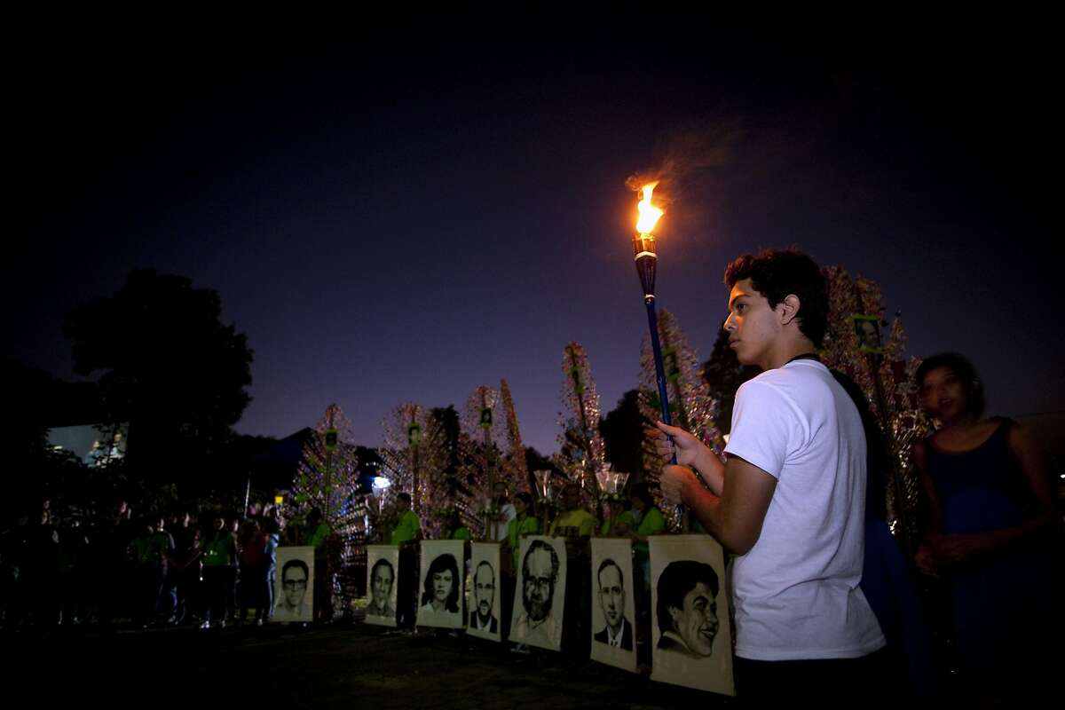 People hold pictures of slain Jesuit priests as they attend a candlelight vigil marking the 20th anniversary of the massacre in San Salvador in November 2009.