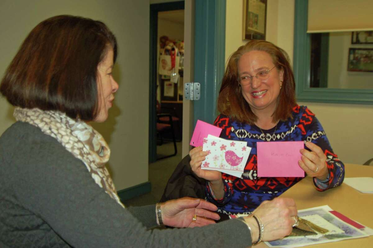 Joan Stewart Pratt, at right, presents a valentine signed by Kids in Crisis supporters to the organizationís Executive Director Shari Shapiro.