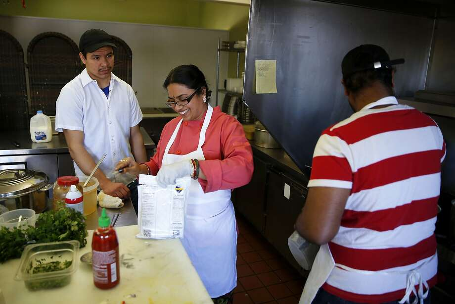 Roberto Montano (left), owner Veena Kallingal and Naveenkumar Sampally prepare dishes for delivery at Kamakshi's Kitchen in San Carlos. Photo: Connor Radnovich, The Chronicle
