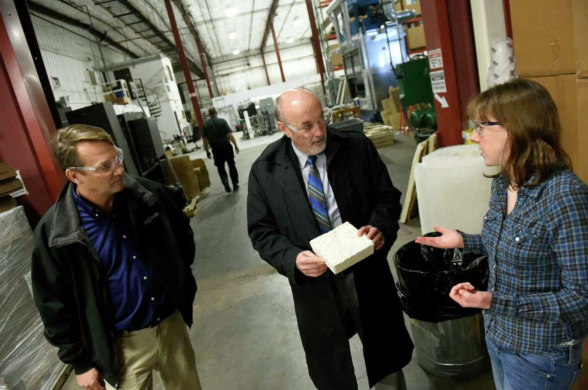 Mayor Patrick Madden, center, holds protective packaging while production manager Katie Malysa, right, explains it's made from mushrooms on Tuesday, Feb. 16, 2016, at Ecovative Design in Troy, N.Y. At left is Andy Ross of Ross Valve. (Cindy Schultz / Times Union)