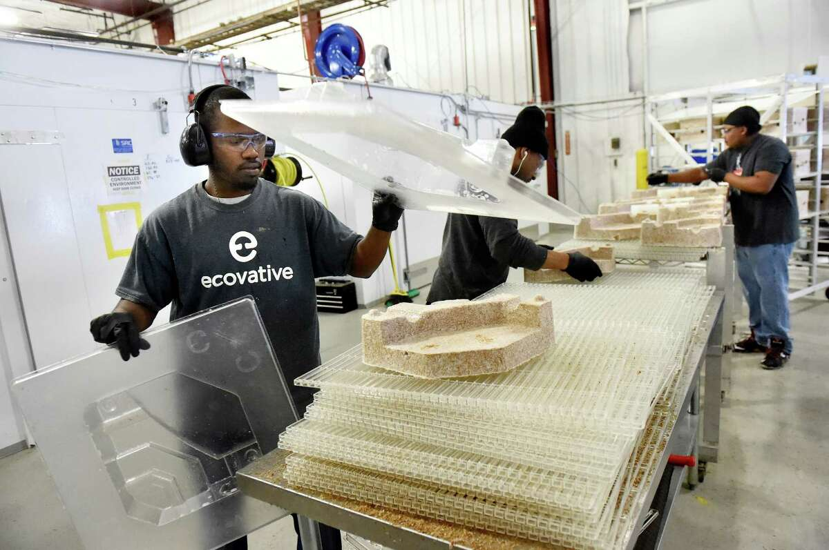 Machine operators move protective packaging material, that's made from mushrooms, from molds to a cart on Tuesday, Feb. 16, 2016, at Ecovative Design in Troy, N.Y. From left are Aaron Ford, Lance Tucker and Aldwin Berry. (Cindy Schultz / Times Union)