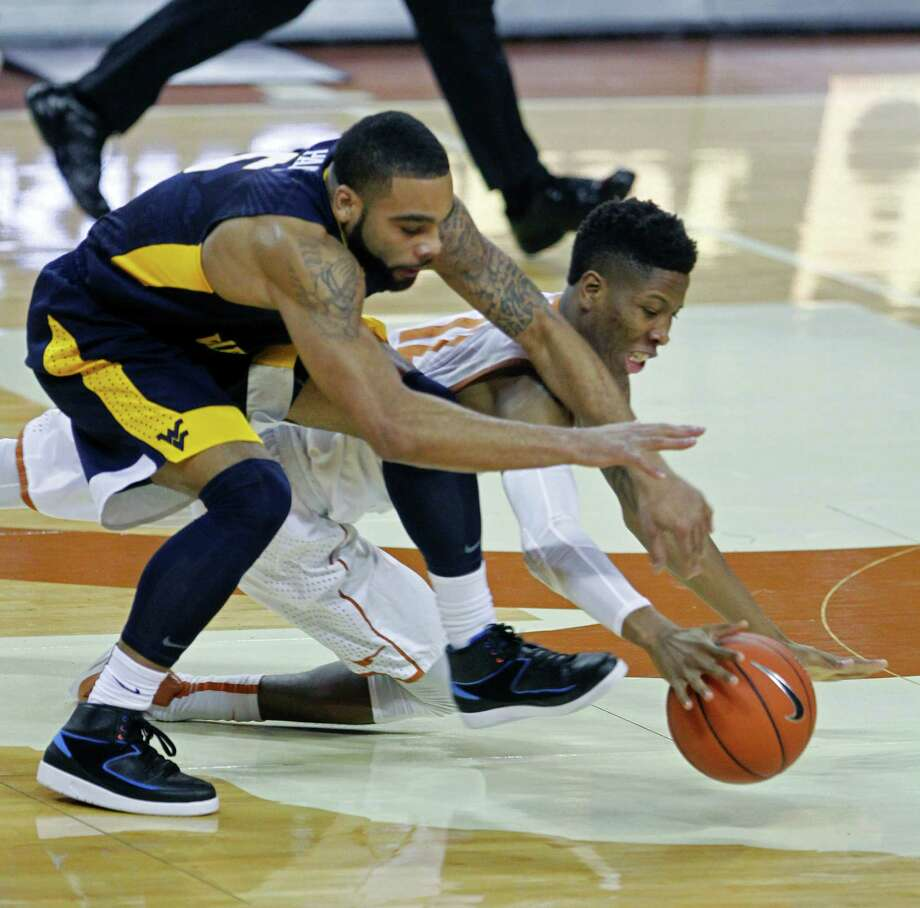 Texas guard Kerwin Roach, right, fights for the loose ball against West Virginia guard Jaysean Paige, left, during the first half of an NCAA college basketball game, Tuesday, Feb. 16, 2016, in Austin, Texas. (AP Photo/Michael Thomas) Photo: Michael Thomas, Associated Press / FR65778 AP