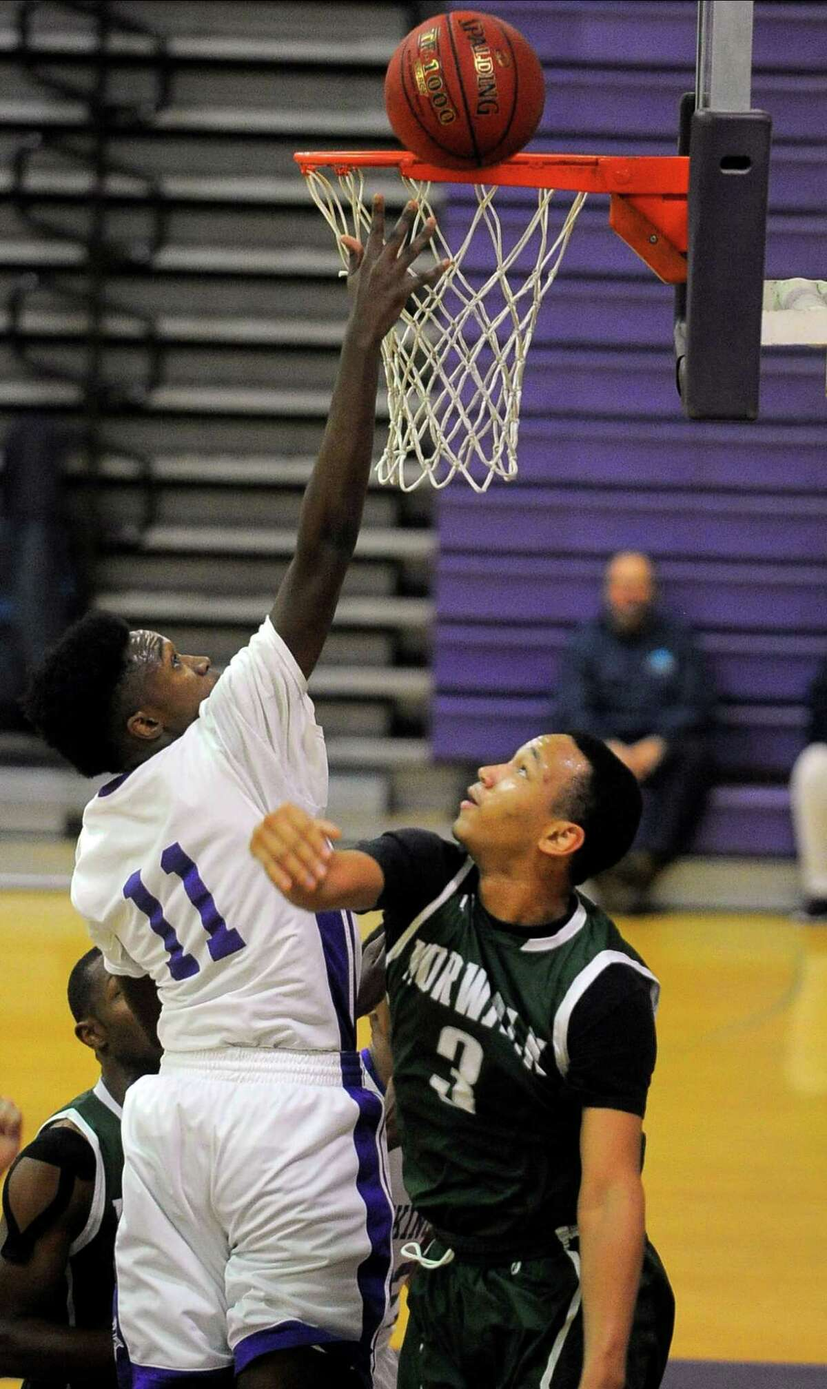 Westhill center Lenold August (11) taps the ball in over Norwalk forward Alex Jerome (3) in the first half of a FCIAC boys basketball game in Stamford, Conn. on Feb. 16, 2016. Westhill defeated Norwalk 55-46.