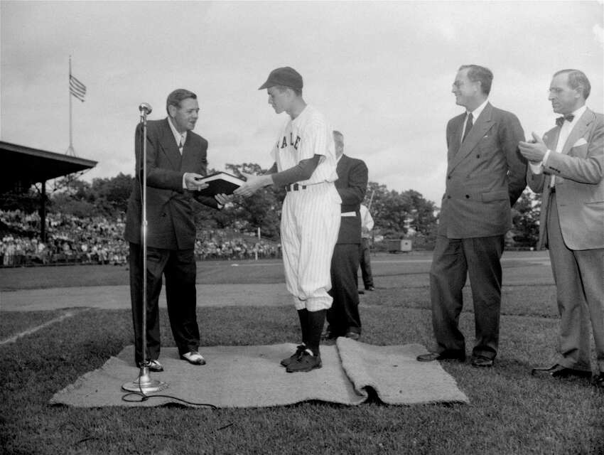 Babe Ruth, left, presents to Yale baseball captain George Bush the original manuscript of