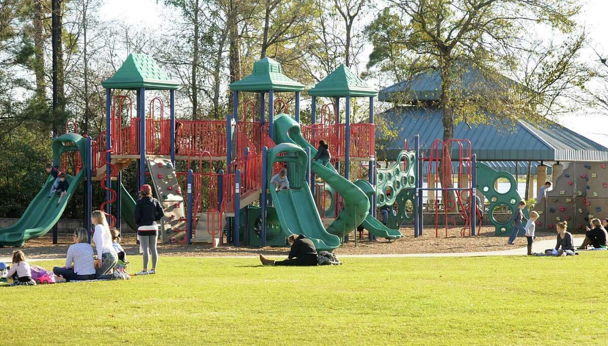 Children play on the playground equipment at Northshore Park, 2505 Lake Woodlands Drive. Photograph by David Hopper