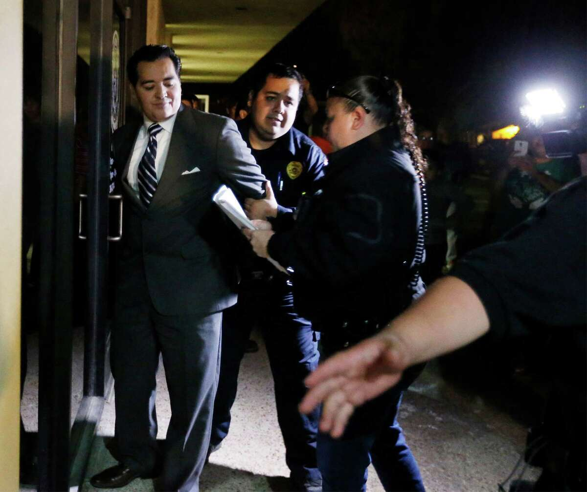 Crystal City Mayor Ricardo Lopez is escorted from City Hall after a scuffle Tuesday night.