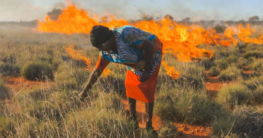"A Martu hunter-gatherer in Australia burns brush in traditional way of gathering goana lizards, a traditional Aboriginal food. A still from ""Cooked,"" a new Netflix documentary series airing February 19, 2016 that is based on the book by Michael Pollan. Photo: Courtesy Of Netflix"