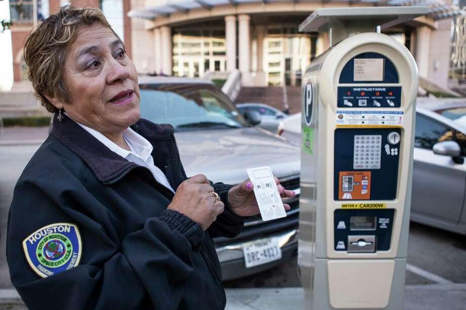 Olga Valdez, parking compliance officer, explains how to use the city's new parking meters on Feb. 16, 2016, in Houston. Photo: Brett Coomer, Houston Chronicle / © 2016 Houston Chronicle