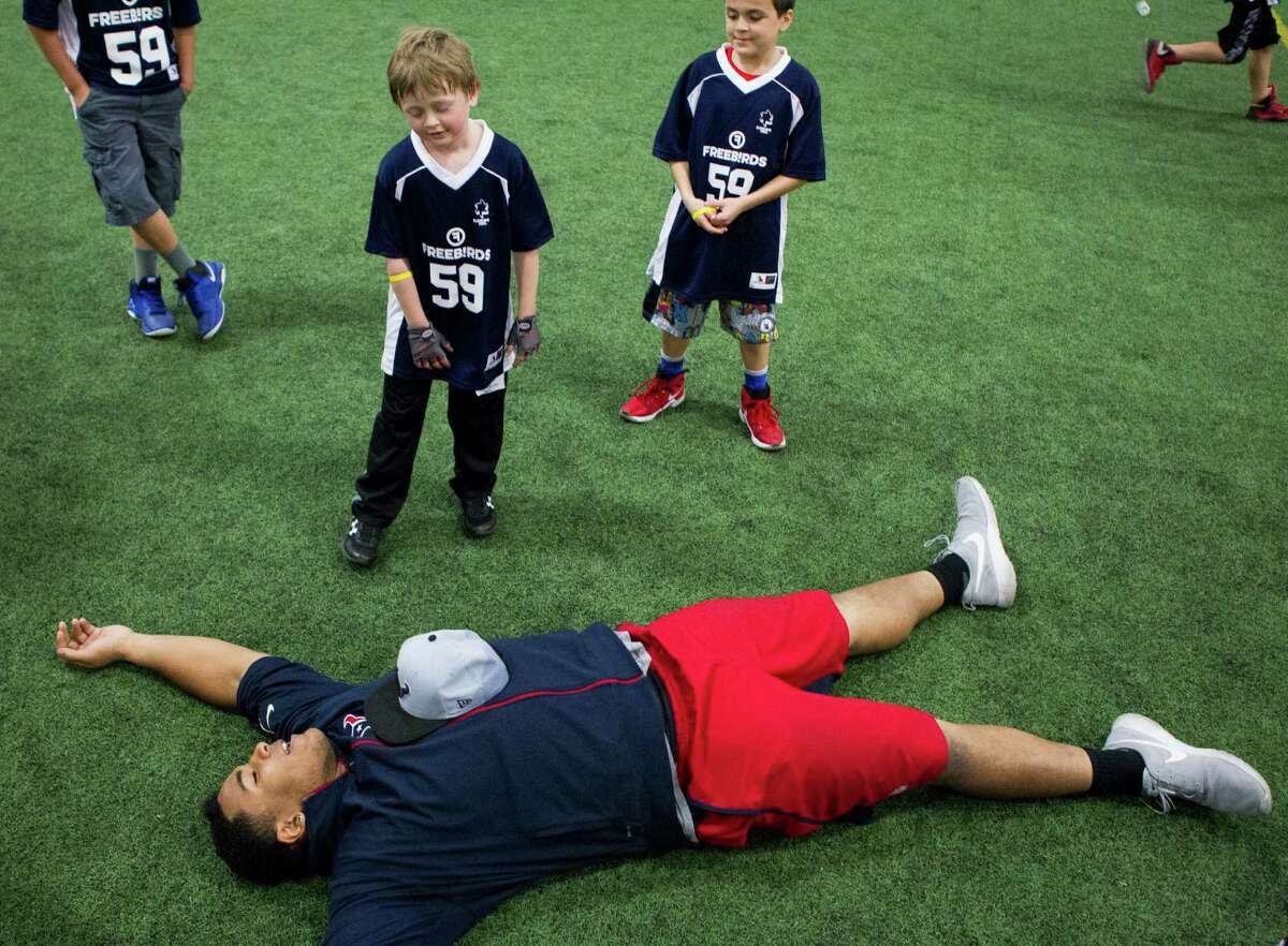 Houston Texans defensive end Christian Covington lies on the turf at Southwest Indoor Soccer after running a race with a group of children from the Sunshine Kids organization and their siblings on Wednesday, Feb. 17, 2016, in Stafford. More than 100 young cancer patients and their siblings participated in the event, learning and playing football skills games.