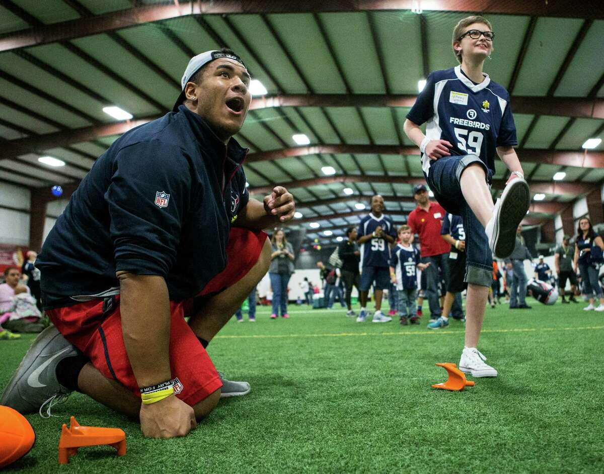 Houston Texans defensive tackle Christian Covington reacts after Avery Speaks kicked a football during a football training camp for the Sunshine Kids at Southwest Indoor Soccer on Wednesday, Feb. 17, 2016, in Stafford. More than 100 young cancer patients and their siblings participated in the event, learning and playing football skills games.